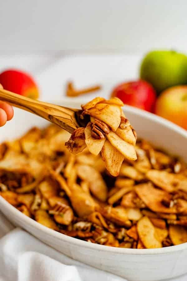 Wooden spoon holding a spoonful of healthy baked sliced apples over an oval white casserole dish filled with baked apples.