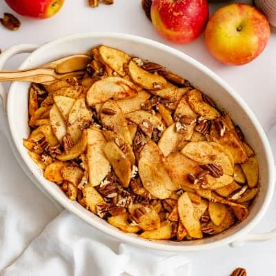 Large white oval casserole dish filled with healthy baked sliced apples with a wooden spoon in the apples with apples in the background.