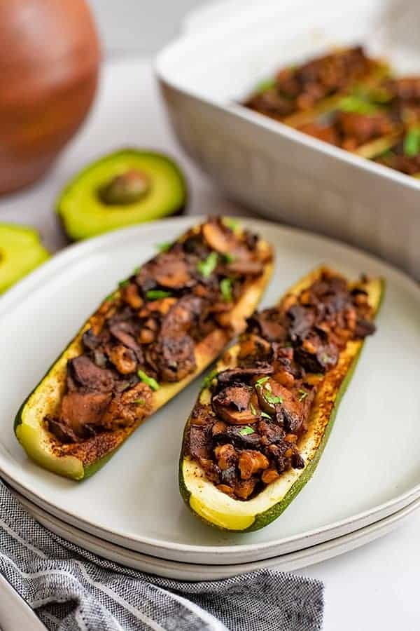 Overhead shot of Two Mexican Stuffed Zucchini Boat Recipe on 2 white plates stacked on top of each other with an avocado in the background