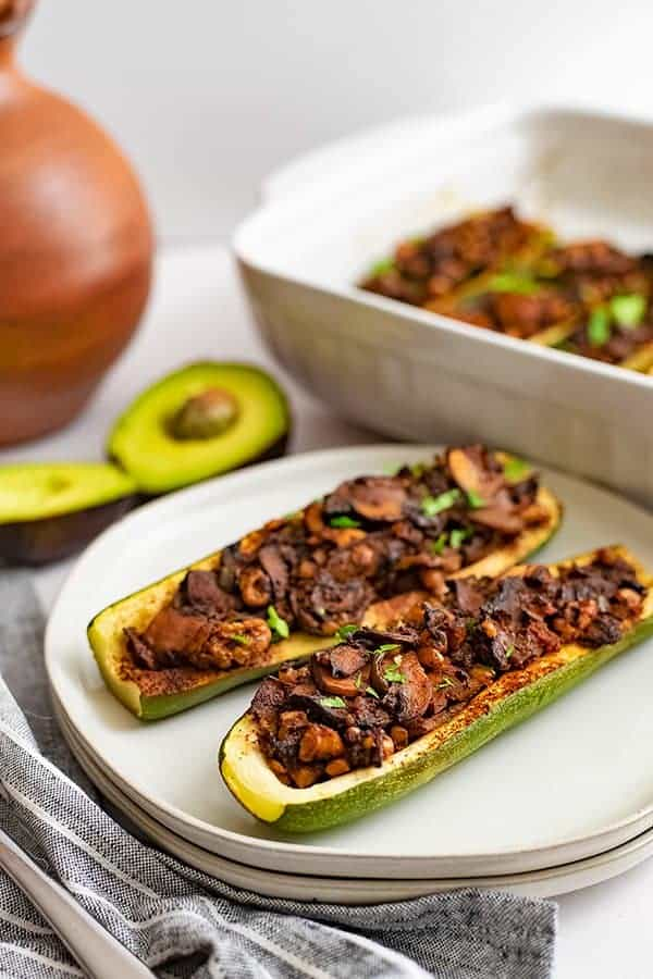 Two Mexican Stuffed Zucchini Boat Recipe on 2 white plates stacked on top of each other with an avocado in the background