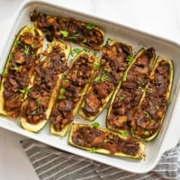 White ceramic dish filled with Mexican Vegetarian Stuffed Zucchini boat recipe over a blue lined napkin