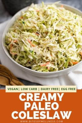 Large white bowl filled with creamy paleo coleslaw on a white napkin with a wooden spoon in the front left of the photo. There is pinterest text on the bottom of the photo