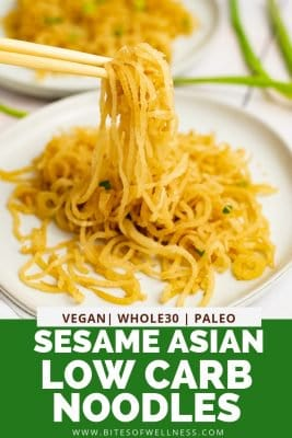 White plate filled with sesame Asian low carb noodles with chopsticks picking up the noodles, bringing the noodles into focus with pinterest text on the bottom