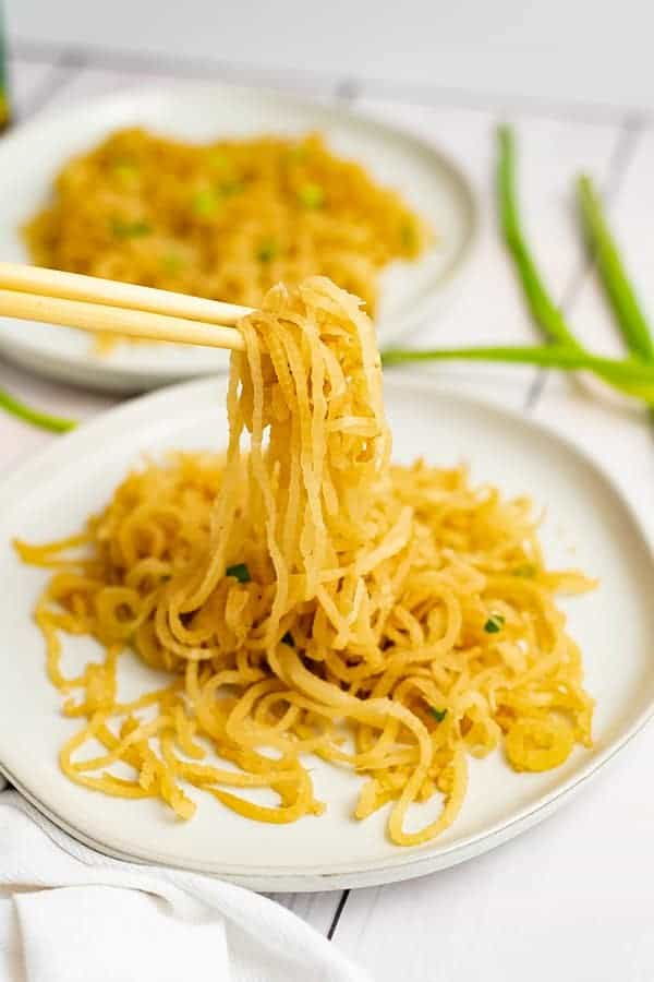 White plate filled with sesame Asian low carb noodles with chopsticks picking up the noodles, bringing the noodles into focus