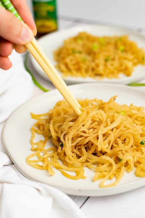 Chopsticks being held by a hand on the left side of the photo picking up sesame asian low carb noodles on a white plate with a white napkin on the left side of the plate.