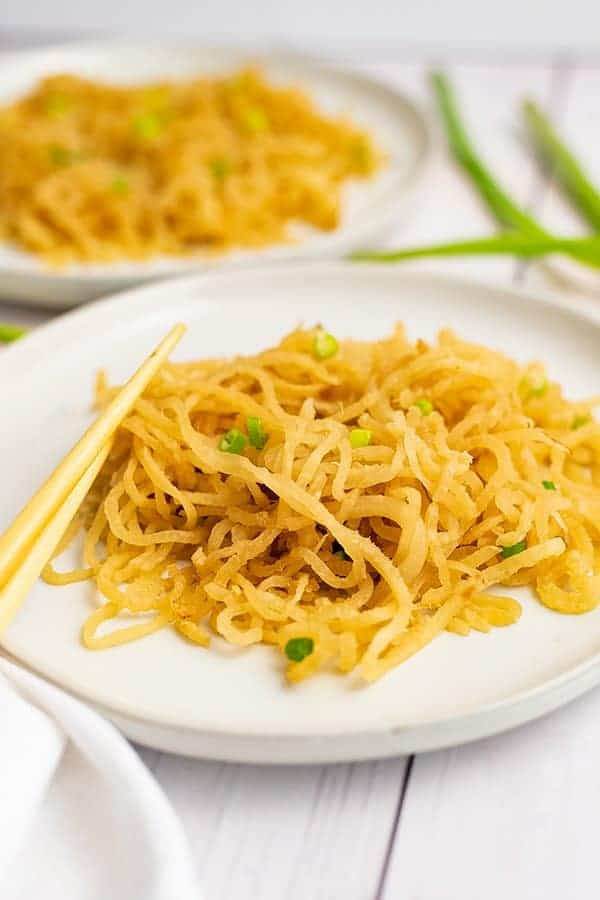 White plate filled with sesame asian low carb pasta with chopsticks sitting on the plate and a white napkin under the plate. There are green onions in the background