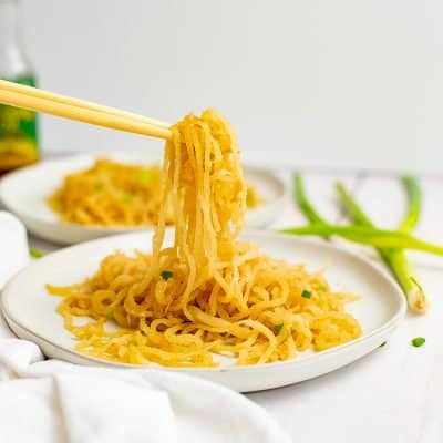 White plate filled with sesame Asian low carb noodles with chopsticks picking up the noodles, bringing the noodles into focus with green onions in the background