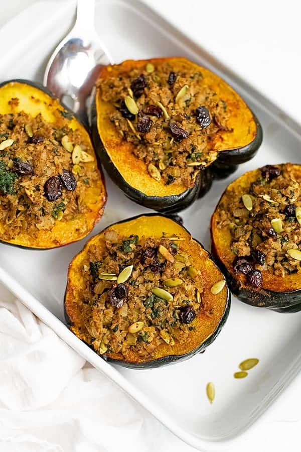 Ceramic white baking pan with 4 stuffed acorn squash in the pan with extra pumpkin seeds sprinkled around.
