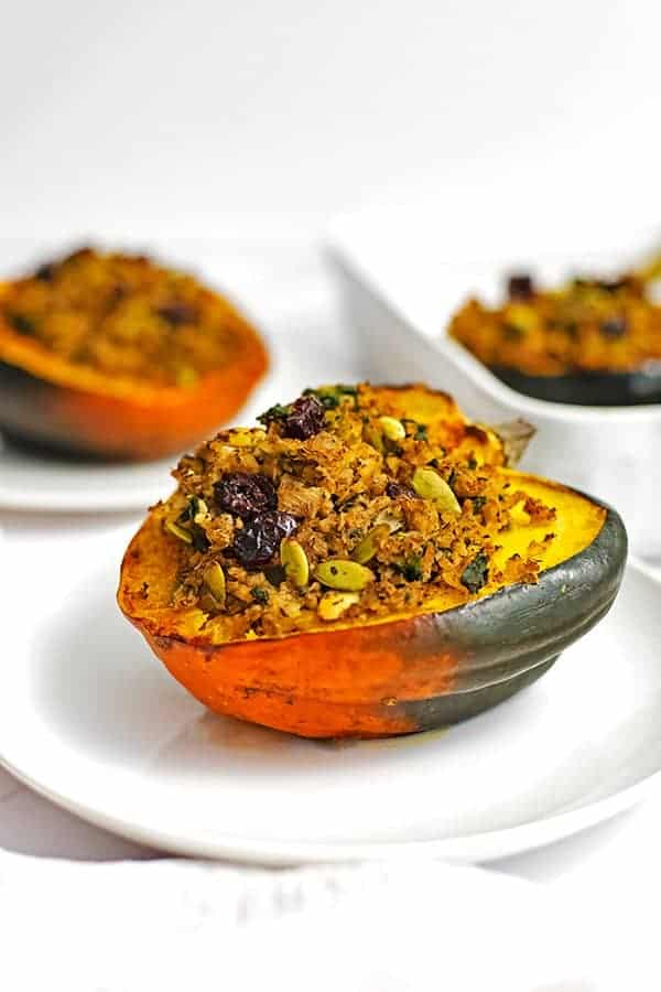 Stuffed acorn squash recipe on a white plate with a second acorn squash in the background