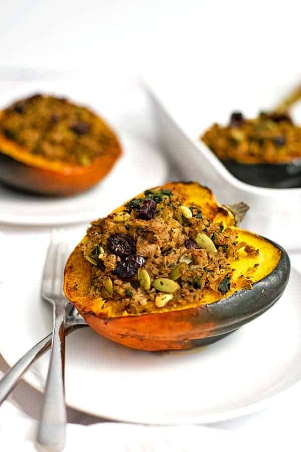 Stuffed acorn squash on a white plate with 2 forks on the plate and a stuffed acorn squash in the background