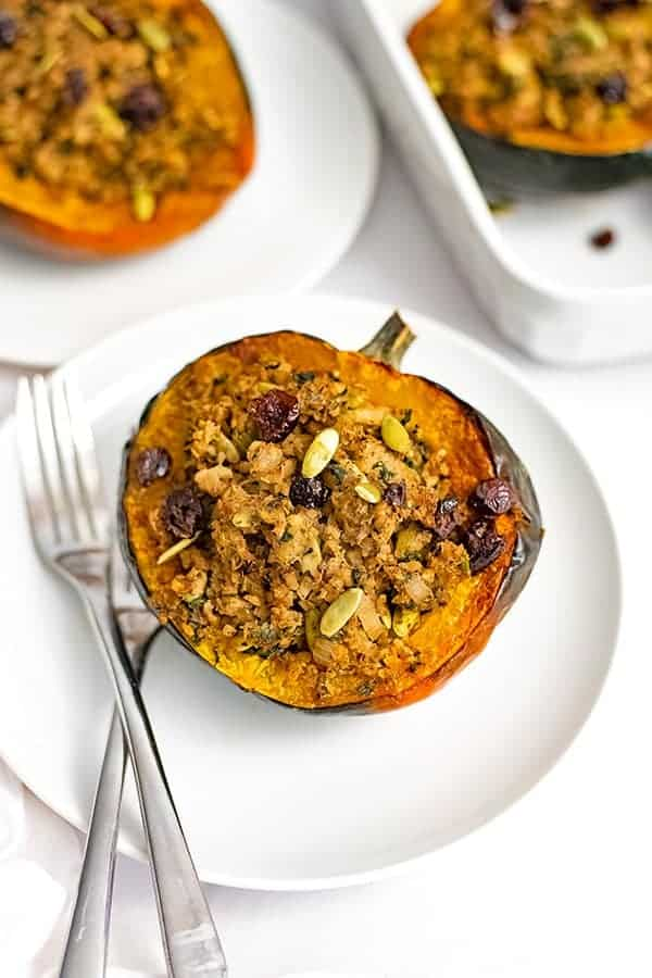Overhead shot of stuffed acorn squash recipe on a white plate with two forks on the plate