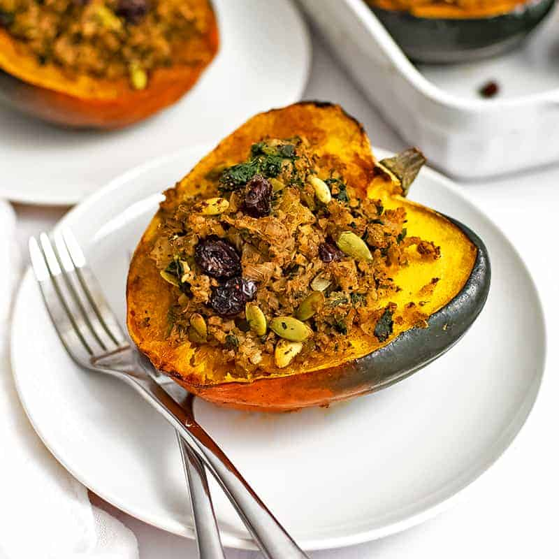 Overhead shot of stuffed acorn squash recipe on a white plate with two forks on the plate with a white serving dish in the background