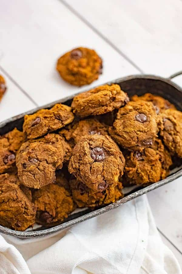 Overhead shot of a silver basket filled with butternut squash chocolate chip protein cookies with a white napkin in the front of the basket
