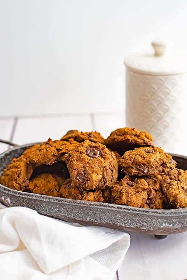 Metal basket filled with butternut squash chocolate chip protein cookie recipe with a white cookie jar in the background