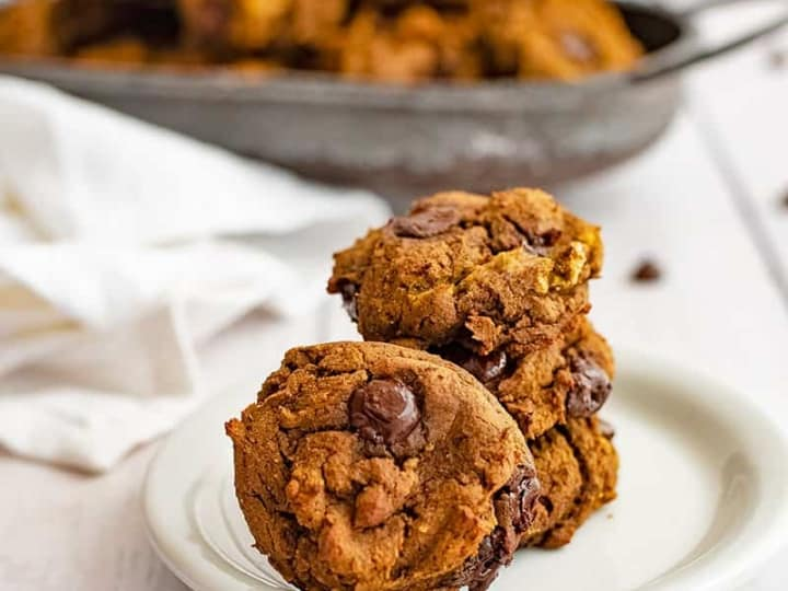 White plate with healthy butternut squash chocolate chip protein cookie recipe stacked in a pile with a basket of cookies in the background