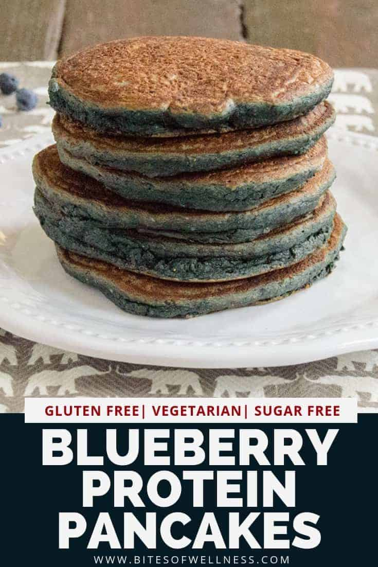 Stack of blueberry pancakes on a white plate with a grey napkin underneath. Pinterest text on the bottom