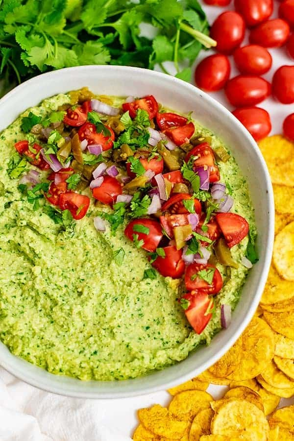 Overhead shot of jalapeno cilantro hummus with plantains, cherry tomatoes and cilantro around the bowl.
