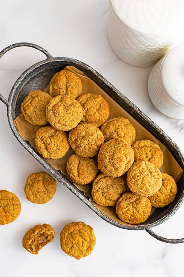 Basket filled with gluten free almond flour muffins over a white table.