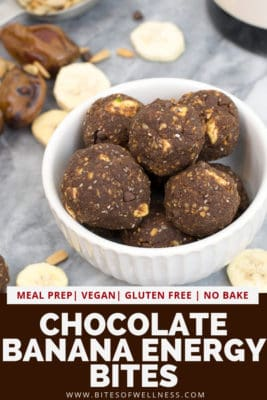 Bowl filled with dobuel chocolate banana energy bites with dried bananas around the bowl. Pinterest text on the bottom of the photo