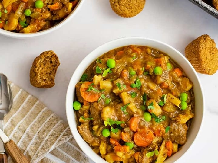 Bowl of easy beef stew (made in instant pot) with muffins around the bowl. Brown striped napkin with wooden spoons to the left