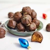 Small green plate filled will gingerbread truffles with a gingerbread truffle with a bite removed in front of the plate. The plate is surrounded by holiday decorations