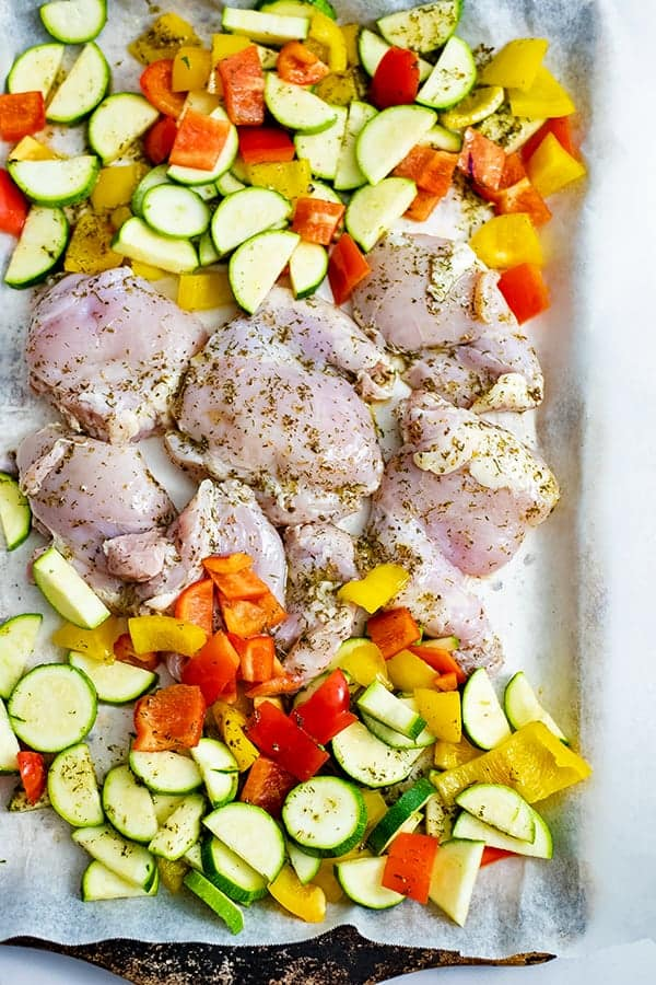 Greek Chicken Marinade Sheet Pan Dinner before the oven. Raw chicken and veggies on a parchment paper lined baking sheet