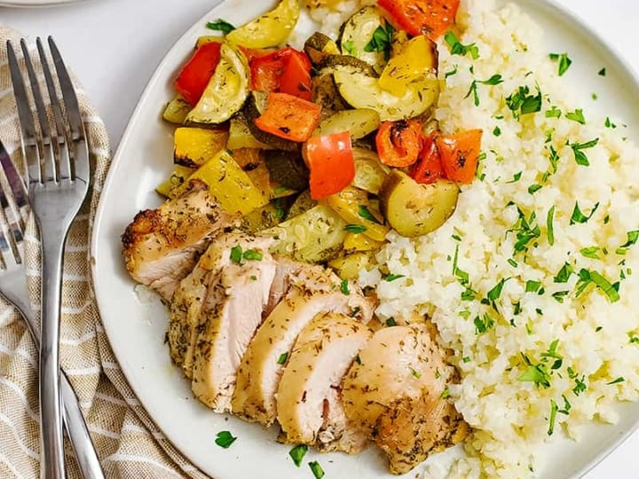 Overhead shot of white dish filled with greek chicken marinade with two forks on the left of the plate over a brown napkin