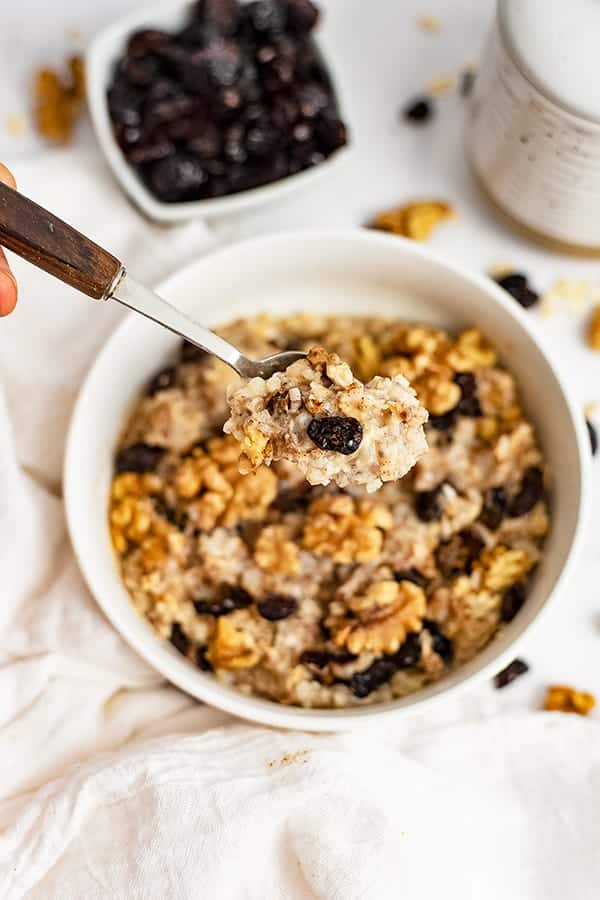 White bowl filled with Walnut Cranberry High Protein Oatmeal with a spoon with a wooden handle hovering over the bowl with a scoop of oatmeal in the spoon
