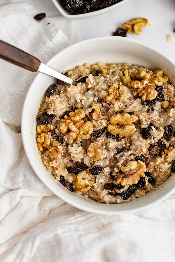 White bowl filled with Walnut Cranberry High Protein Oatmeal with a spoon with a wooden handle in the oatmeal
