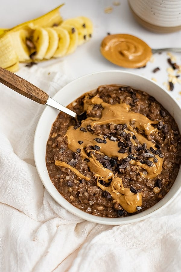 Zoomed in shot of a white bowl filled with Chocolate Peanut Butter Swirl High Protein Oatmeal with a spoon with a wooden handle in the oatmeal