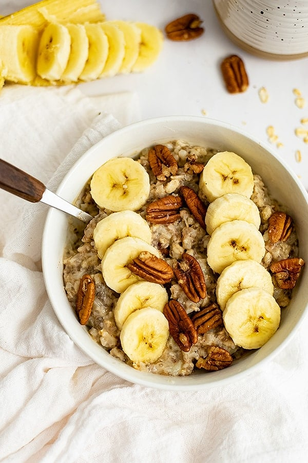 White bowl filled with Banana Nut High Protein Oatmeal with a spoon with a wooden handle in the oatmeal
