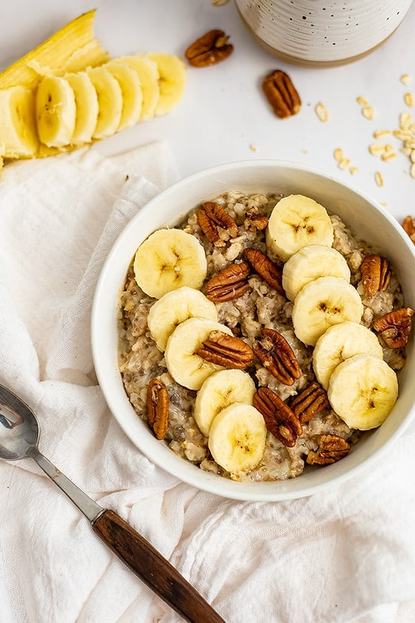 White bowl filled with Banana Nut high protein oatmeal with a spoon to the left of the bowl over a white napkin. Sliced banana in the background