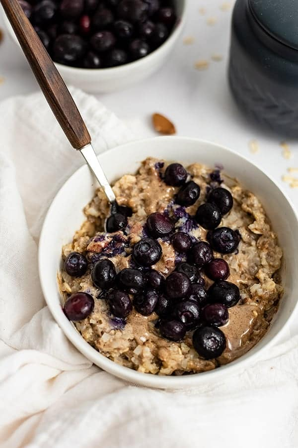 White bowl filled with Blueberry Almond High Protein Oatmeal with a spoon with a wooden handle in the oatmeal