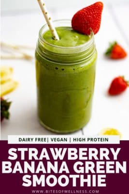 Large mason jar filled with strawberry banana green smoothie with a straw sticking out from the smoothie and a strawberry on the rim of the glass. Pinterest text on the bottom of photo