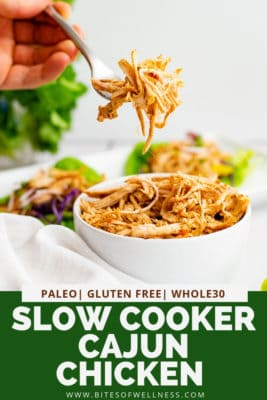 Bowl of Whole30 slow cooker cajun chicken with a hand holding a fork full of the cajun chicken above the bowl. Pinterest text on the bottom of the photo