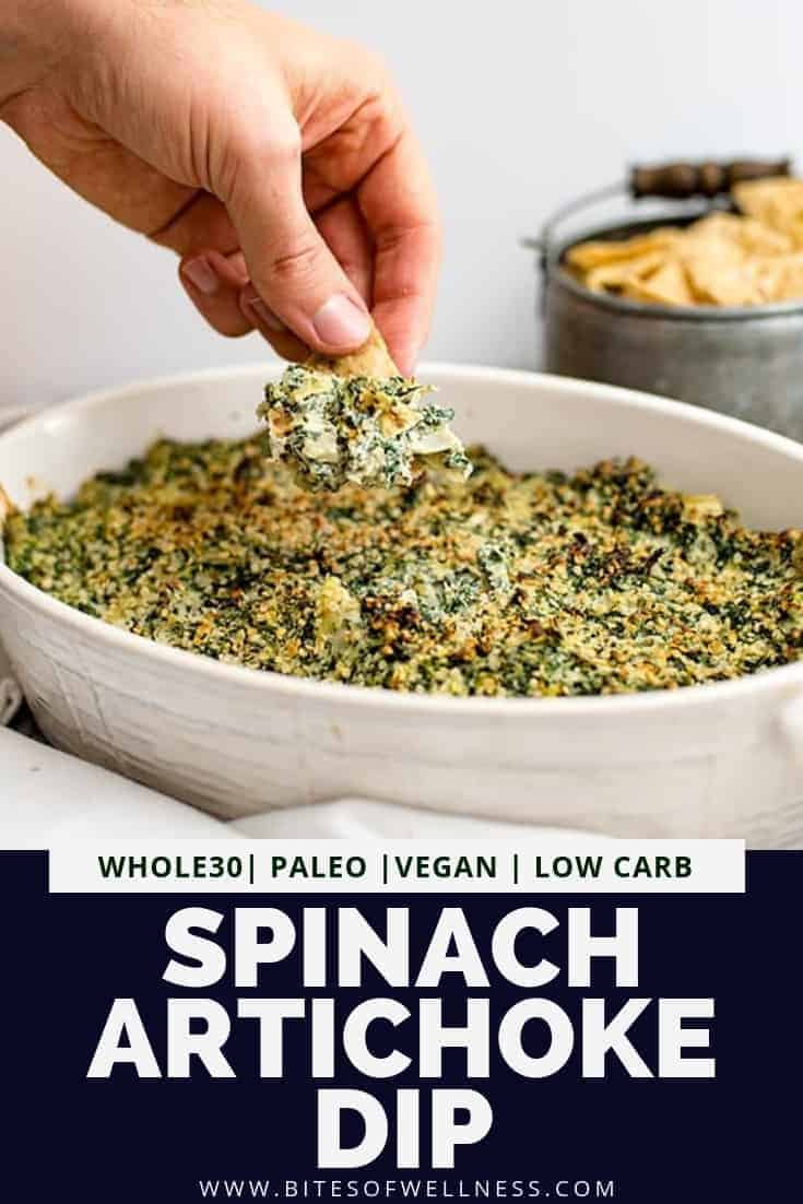 White casserole dish with whole30 spinach artichoke dip with a hand dipping a chip into the spinach artichoke dip. Pinterest text on the bottom