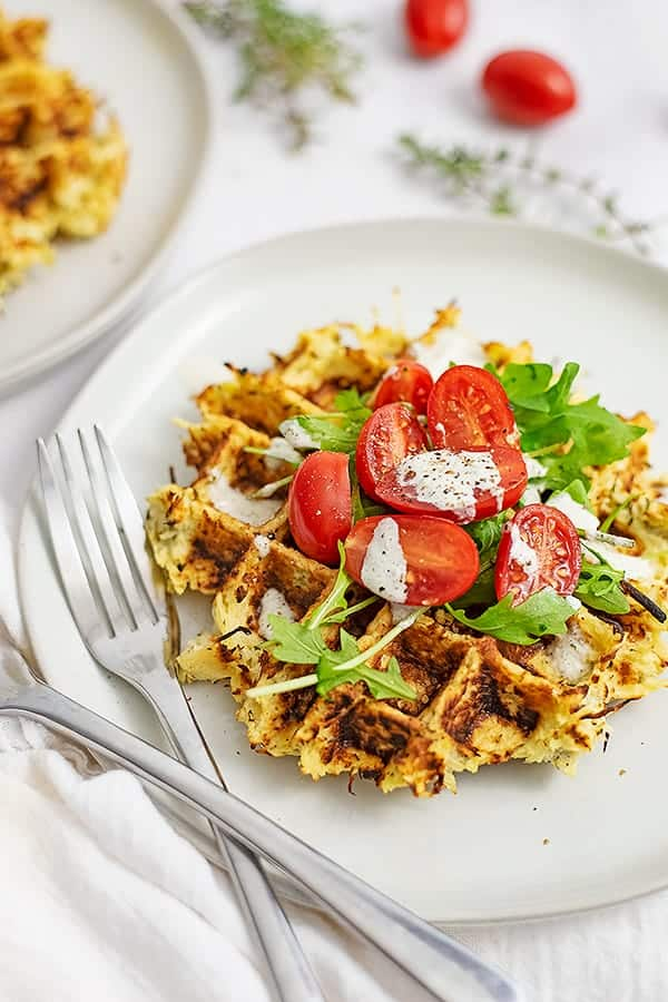 Close up of white plate with parsnip savory waffle recipe topped with arugula, tomatoes and dressing with two forks on the left side of the plate.