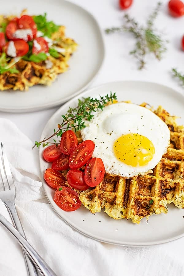 5 ingredient parsnip waffle savory waffle recipe on a white plate topped with a fried egg, tomatoes and sprigs of thyme. Second savory parsnip waffle in the background