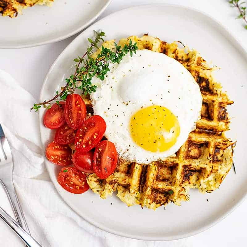 Overhead shot of parsnip savory waffle recipe topped with a fried egg, halved cherry tomatoes and thyme leaves