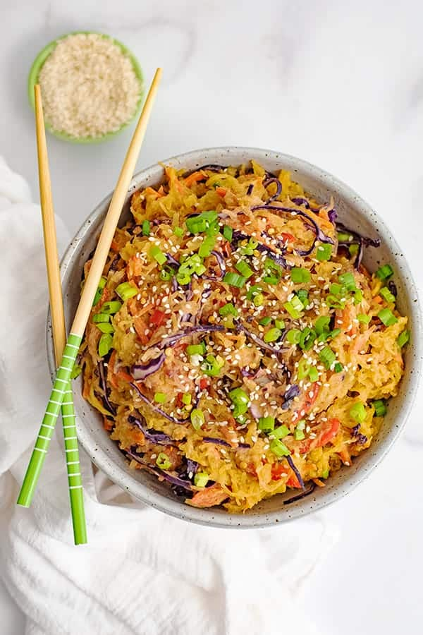 Overhead shot of a large bowl filled with vegan creamy Asian spaghetti squash recipe with chop sticks resting on the bowl and a bowl of sesame seeds in the background