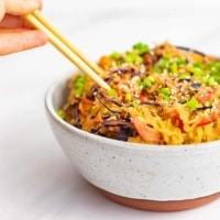 A large bowl with a rust colored bottom filled with creamy Asian vegan spaghetti squash recipe with chopsticks being held, plunging into the left side of the bowl