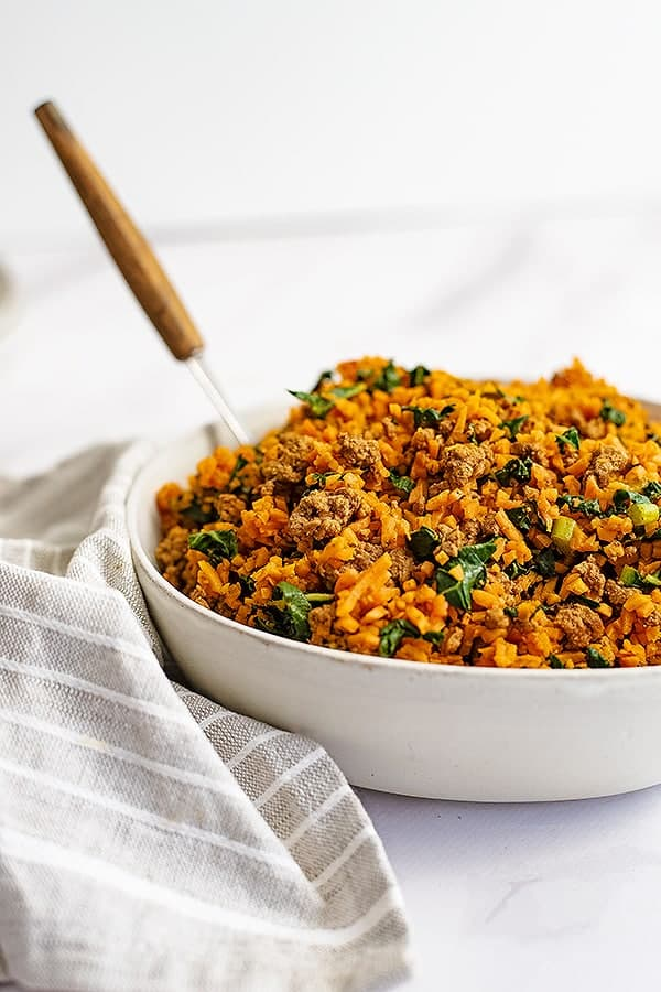 Large white bowl filled with the easy ground beef and sweet potato rice breakfast skillet recipe with a grey striped napkin to the left of the bowl and a wooden handled spoon in the bowl.