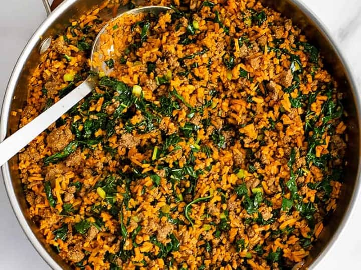 Overhead shot of large skillet filled with easy ground beef sweet potato rice breakfast skillet recipe with a large silver serving spoon resting in the skillet