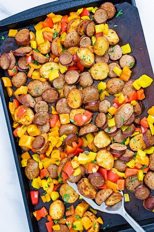 Over head shot of a sheet pan filled with easy tureky kielbasa and potatoes sheet pan dinner with a silver spatula in the bottom right corner