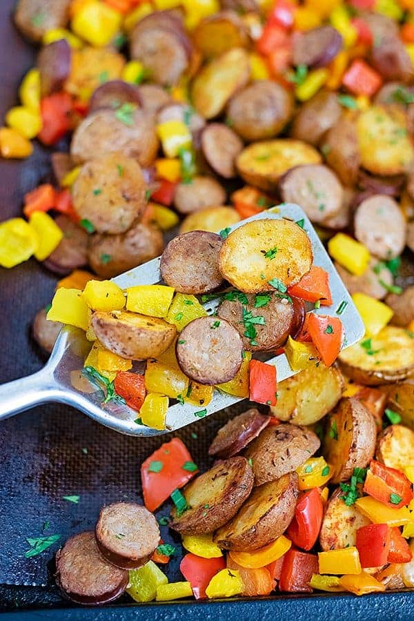 Silver spatula scooping up a serving of easy turkey kielbasa and potato sheet pan dinner