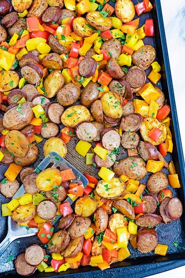 Sheet pan filled with easy tureky kielbasa and potatoes sheet pan dinner with a silver spatula in the left bottom corner