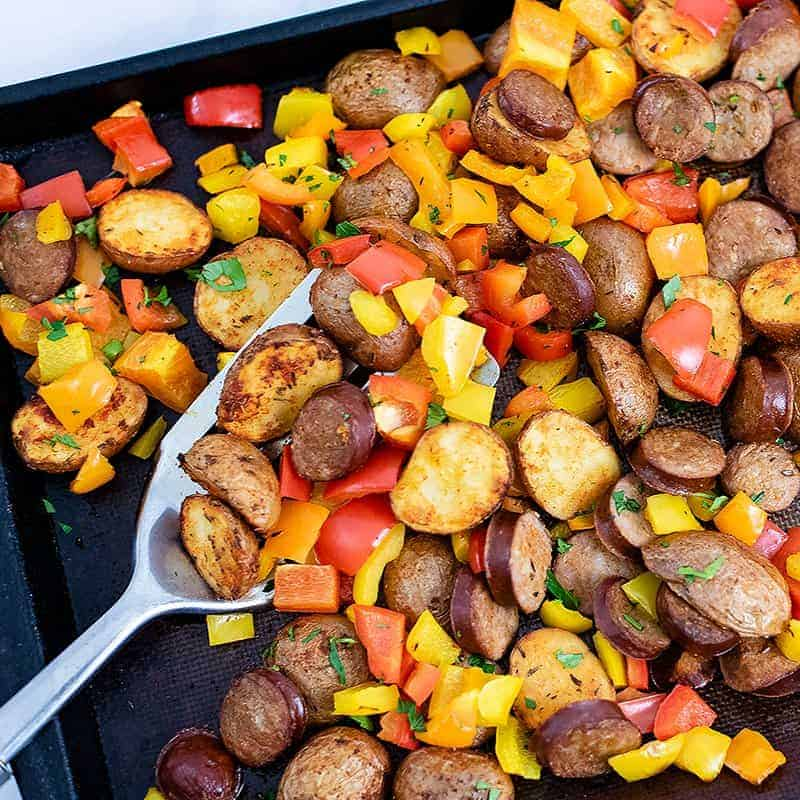 Sheet pan filled with easy tureky kielbasa and potatoes sheet pan dinner with a silver spatula in the center of the photo