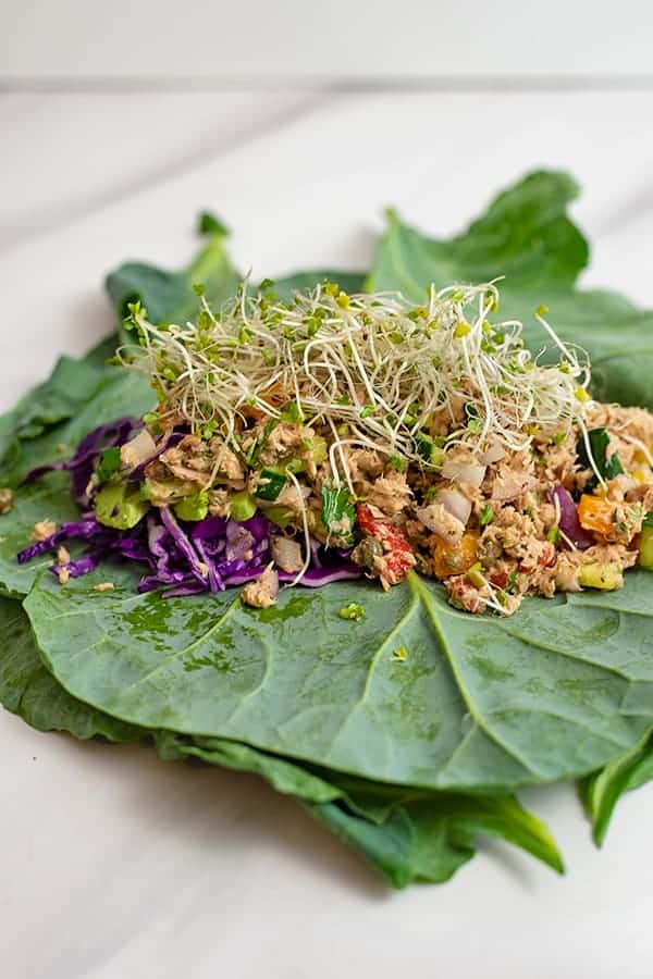 Healthy Mediterranean tuna salad (no mayo) on a collard green wrap with red cabbage and sprouts