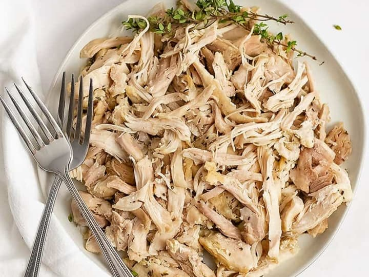 Overhead shot of a plate of Instant Pot Shredded Chicken Thighs with two forks on the left side of the plate and a white napkin