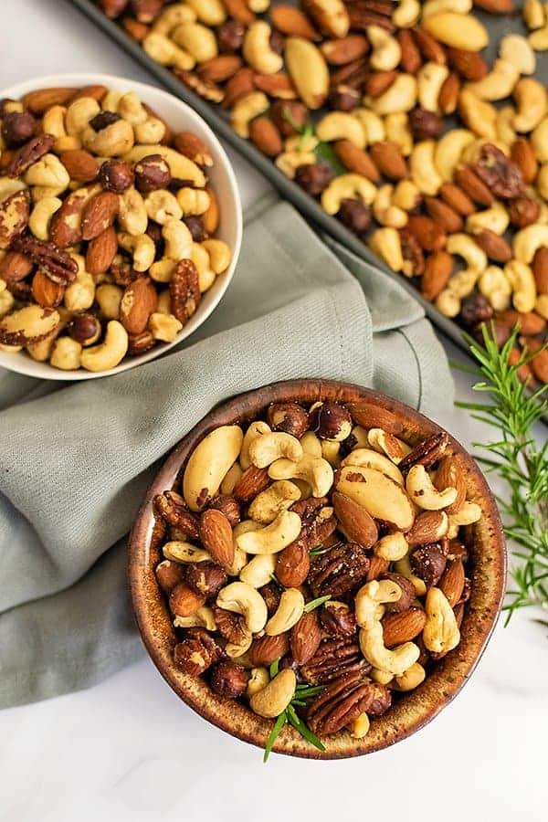 Overhead shot of two bowls of rosemary savory spiced nuts with a grey napkin between the bowls and a baking sheet full of nuts in the background